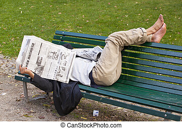 Man reading the newspaper lying on the bench