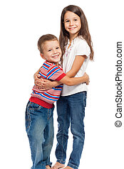 Two smiling little kids hugging each other, isolated on...