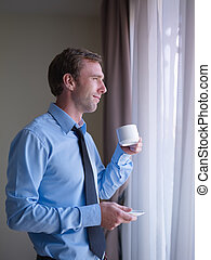 Businessman drinking coffee and looking out of window - Mid...