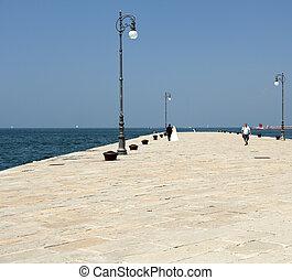 Spouses walking on molo Audace in Trieste