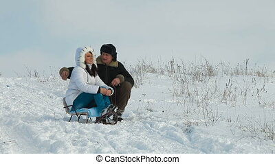 married adult couple on sledge in winter laughing
