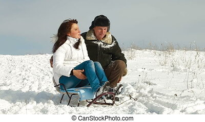 couple sitting on sledge - adult couple sitting on sledge...