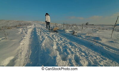 woman with a sledge uphill on a winter evening