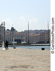 Spouses walking on molo Audace in Trieste