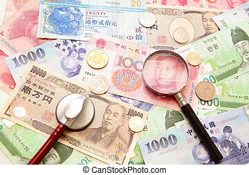 asian currency, magnifying glass and stethoscope with...