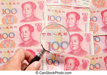 chinese money (currency) and magnifying glass, concept for...