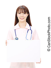 Young asian female nurse holding a blank board