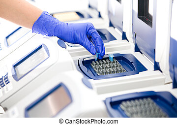 Scientist with DNA copying, Real-time cycler, wide -...