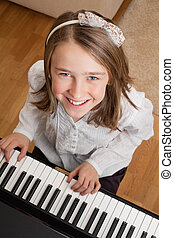 Playing the piano at home - Photo of a happy young girl...
