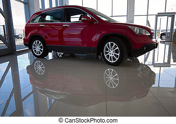 red car - View of car in showroom. His shadow reflected on...