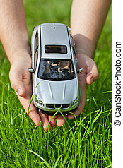 Hands with toy car on grass background.