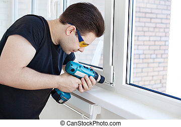 Man worker mounting window on balcony