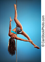 Young pole dance woman on blue background