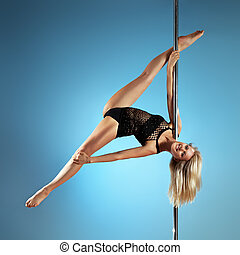 Young pole dance woman on blue background.