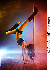 Young pole dance woman with smoke effect.