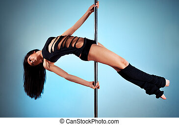 Young pole dance woman. On blue wall background.