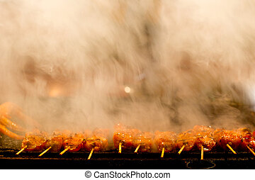barbecue sticks - row of barbecue sticks are being grilled,...