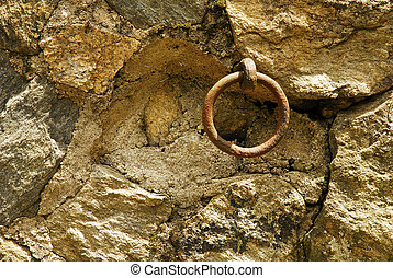 Rusted Ring Embedded in Stone - A rusted ring hangs embedded...