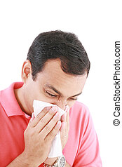 Young man with a cold blowing nose on tissue