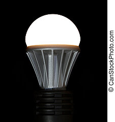 Lit LED Light Bulb - A lit LED bulb isolated on a black...