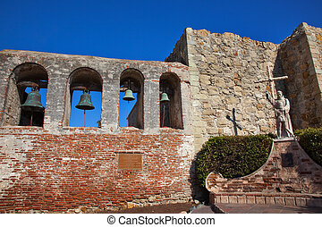 Mission San Juan Capistrano Church Ruins in California.  Brass Bells and Statue of Father Junipero Serra, who founded the Mission in 1775.  Church was destroyed in 1812 by earthquake.
