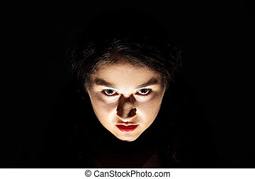 Scary portrait of angry woman against black background
