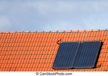 Solar cells on a roof in front of a cloudy sky