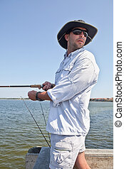 Man Fishing from Pier - Handsome man with sunglasses and...