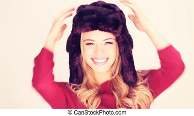 Lively Woman In Fur Hat with her hands to the earflaps...