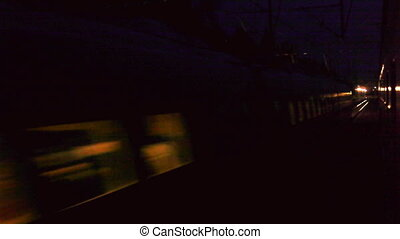 Fast train goes near the other train, night view from train window