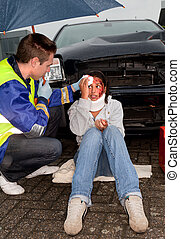 Car accident in the rain - Paramedic taking care of an...