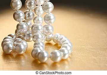 String of pearls on golden surface