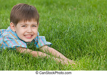 Smiling boy on the green lawn - A smiling boy is lying on...