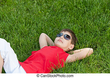 Dreaming boy on the grass - A thoughtful boy is lying on the...