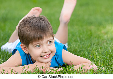 Cheerful boy on the green lawn - A cheerful boy is lying on...