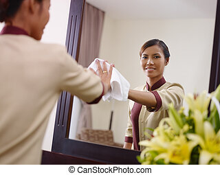 Asian maid working in hotel room and smiling - Portrait of...