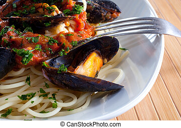 Spaghetti with mussels on wooden table