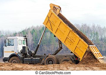 Yellow dump truck - Dump truck unloading a mountain of soil...