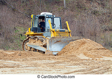 A yellow bulldozer working - Bulldozer leveled layer of sand...