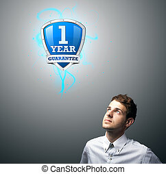 businessman watching on a virtual shield sign - Young...