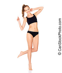 Fitness woman in black sports clothes isolated on white