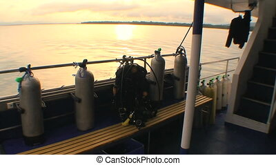 Sunset on a Scuba Boat - The sun setting from the deck of a...