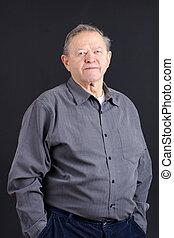 Old man hands in pocket over black - Portrait of an old or...