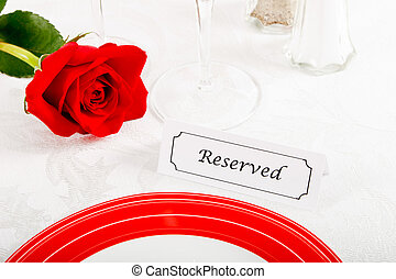 Close up of Reserved Restaurant Table with Red Rose