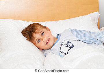 child lies in bed in the bedroom - small child lies in bed...