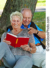mature senior couple in love. read a book
