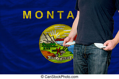 poor man showing empty pockets in front of american state of...