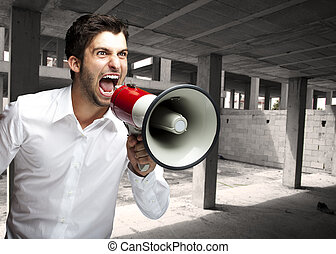 man shouting with megaphone - portrait of angry young man...
