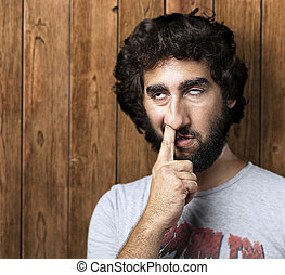 man with finger in nose - portrait of young man with the...