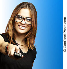 woman with tv control - portrait of young woman with glasses...